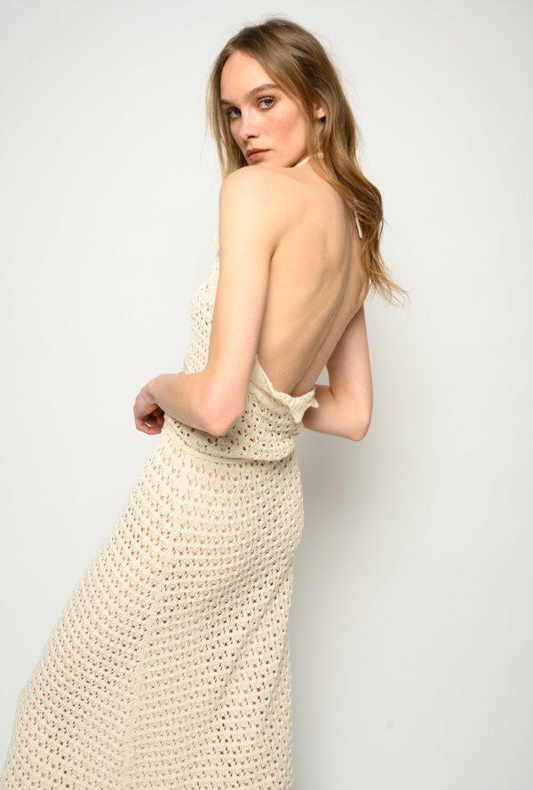 Vestido largo en croché de algodón con escote halter que se ata detrás del cuello, con parte superior perfilada con volante. Cordón ajustable en el talle para personalizar su uso y falda de línea holgada.